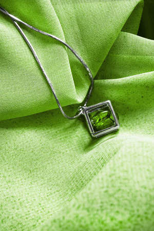 Emerald pendant on a chain on green cloth as a background Stok Fotoğraf