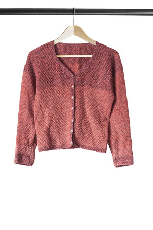 cardigan: Terracotta knitted cardigan on wooden clothes rack isolated over white Stock Photo