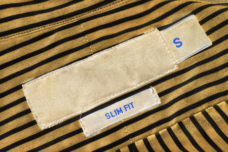 docket: Clothes label lettered slim fit on striped cloth as a background Stock Photo