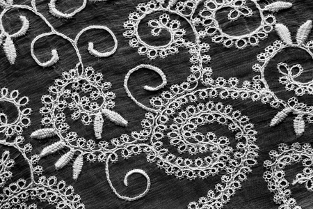 openwork: Vintage white lace on black as a background
