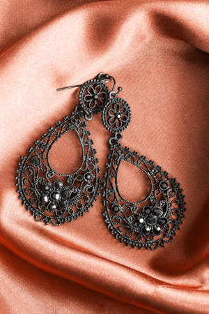 openwork: Black metallic lacy earrings on brown satin as a background Stock Photo