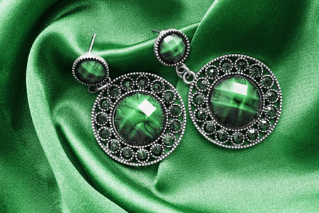 Vintage malachite earrings on green satin as a background