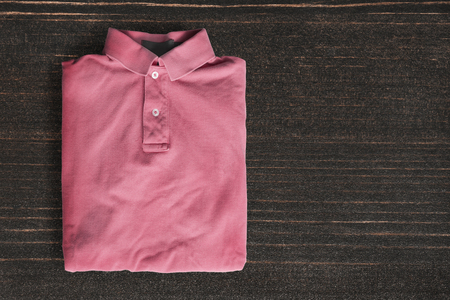 folded: Folded pink polo shirt on dark wooden background