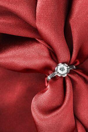 Silver diamond ring on red crumpled silk closeup