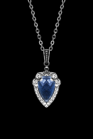 Blue sapphire pendant on silver chain isolated over black Stock Photo