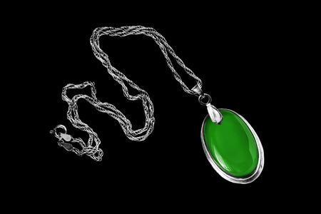 Green emerald medallion on silver chain isolated over black