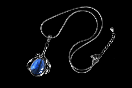Vintage sapphire pendant on silver chain on black background