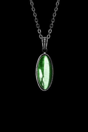 Vintage emerald medallion on silver chain isolated over black