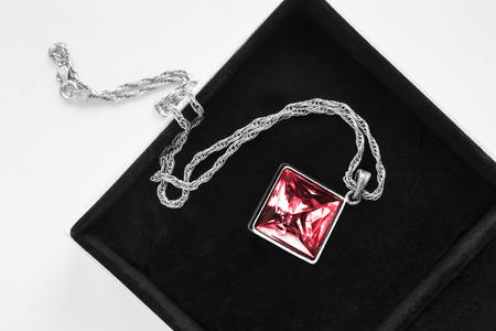 Large red gem pendant on silver chain in jewel box closeup Stock Photo