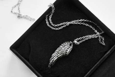 Silver wing pendant on a chain in black jewel box closeup