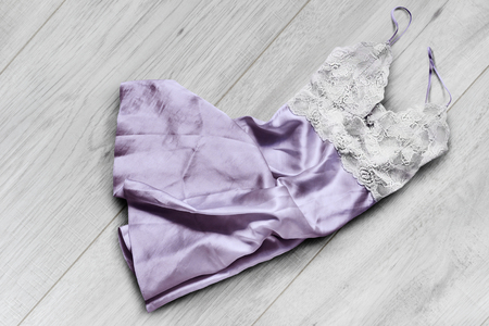 Crumpled satin and lacy nightdress lying on white wooden floor Banco de Imagens