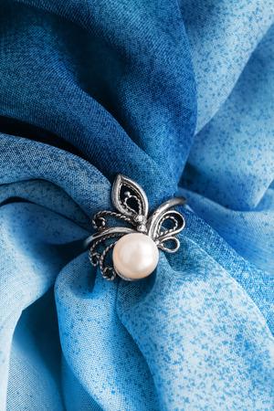 Elegant vintage pearl ring on blue draped silk closeup Stock Photo
