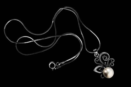 Necklace with a silver pearl pendant on black background