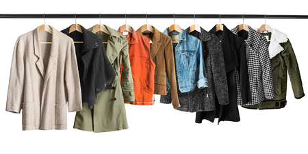 Group of coats and jackets hanging on clothes racks isolated over white Stock Photo