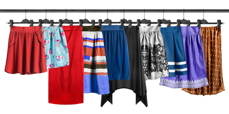 Group of skirt hanging on clothes racks isolated over white Stock Photo