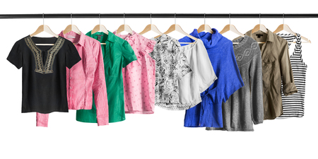 pullovers: Group of shirts and pullovers hanging on clothes racks isolated over white