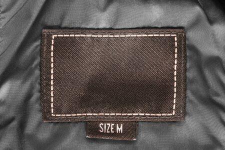 Beschriftete Größe M der Kleidung Aufkleber auf schwarzer Satinnahaufnahme