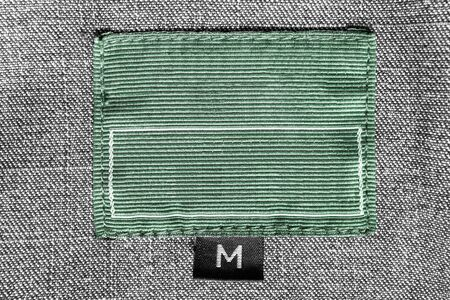 medium size: Green textile clothes label on gray tweed background closeup