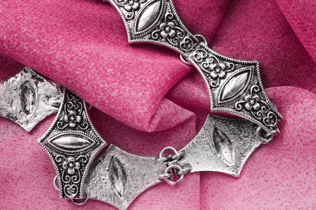 gloss: Vintage silver necklace on pink folded silk closeup