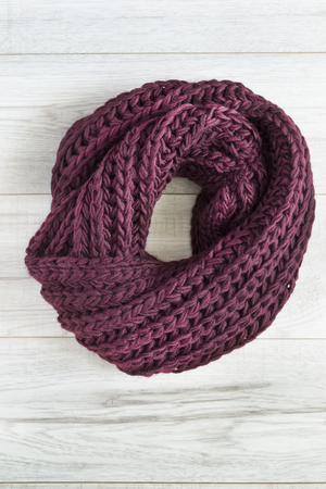 Knitted purple knotted scarf on white wooden background Stock Photo