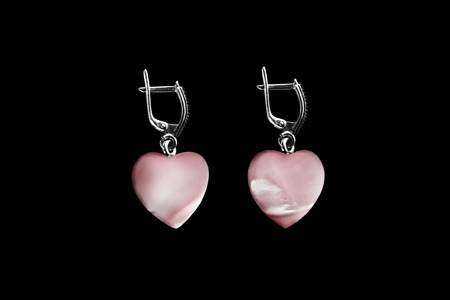 Pink heart shaped nacre earrings isolated over black