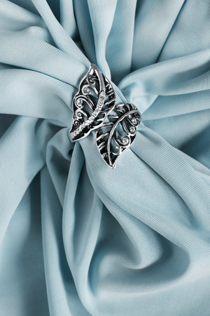 Elegant silver ring with crystals on draped blue silk closeup