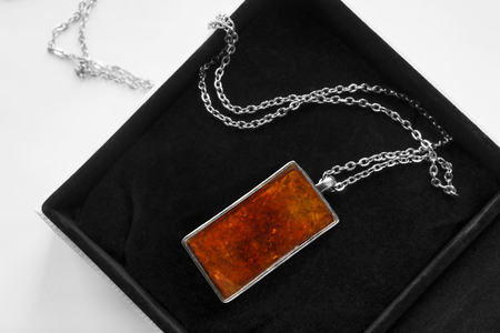 Elegant large amber pendant on a chain in black jewel box closeup Imagens