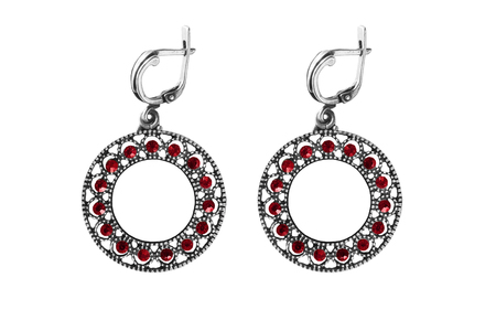 Vintage silver ring shaped earrings with red gems isolated over white