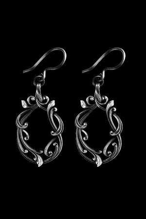 Pair of elegant vintage silver earrings on black background