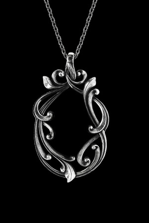 Vintage elegant silver pendant hanging on a chain on black background Stock Photo