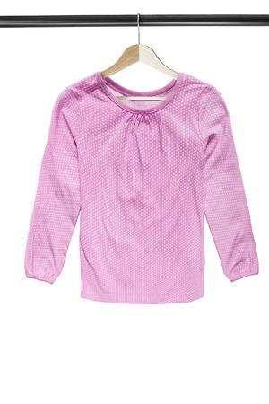 白の上に隔離された木製の服のラックにピンクの綿の水玉ブラウスブラウス