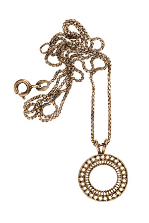 Golden ethnic carved pendant with a chain on white background