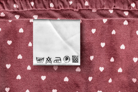 Washing instructions clothes label on red cotton background closeup Stockfoto