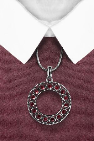 Silver pendant with red gems hanging over knitted sweater with white collar Фото со стока