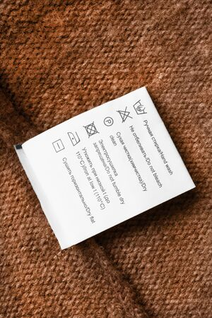 Care clothes label in english and russian languages on brown knitted background