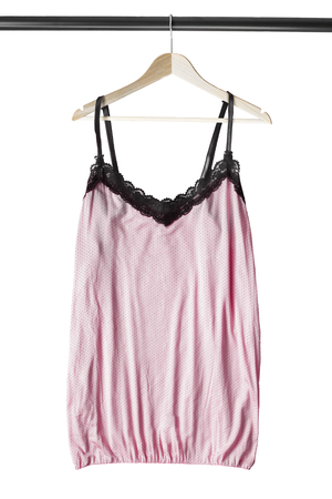 Pink lingerie top with black lace hanging on wooden clothes rack isolated over white