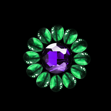 Group of green and purple gems in the shape of a flower isolated over black