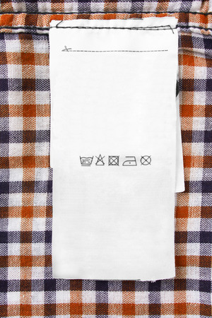 White care clothes label on checkered cotton background closeup