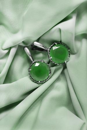 Vintage emerald faceted earrings on pastel green crumpled silk Reklamní fotografie