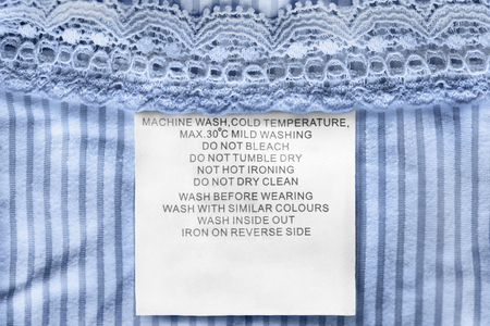 Care clothes label on blue lacy textile background closeup Stockfoto