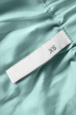XS size clothes label on blue cotton background closeup