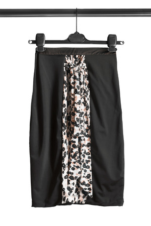 Elegant black silk pencil skirt hanging on clothes rack isolated over white