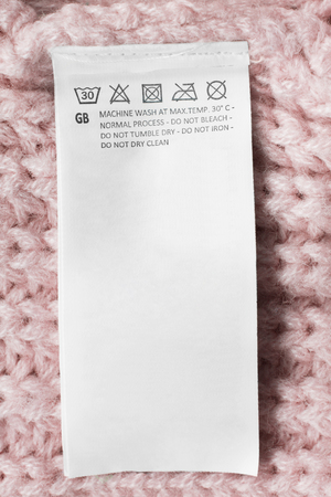 Care clothes label on pink knitted background closeup Stockfoto