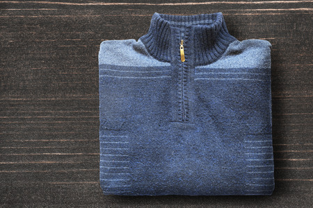 Folded blue sport knitted pullover on dark wooden background