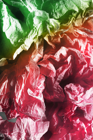 Crumpled pink and green wrapping paper closeup