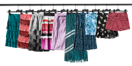 Group of skirts and shorts hanging on clothes racks on white background