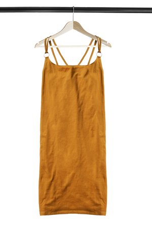Yellow elegant dress hanging on wooden clothes rack isolated over white 免版税图像