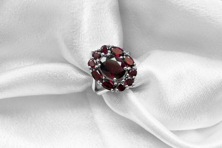 Red ruby luxury ring on white satin background closeup