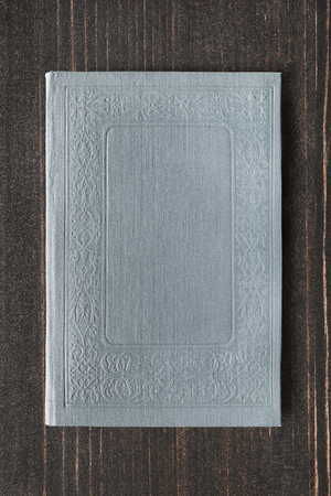 Book with grey blank cover on dark brown wooden background Stock fotó