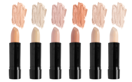 Palette of cream concealer sticks isolated over white